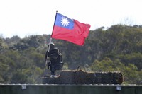A soldier holds a Taiwan national flag during a military exercise in Hsinchu County, northern Taiwan, Tuesday, Jan. 19, 2021. (AP Photo/Chiang Ying-ying)