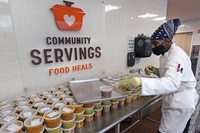 Chef Jermaine Wall stacks containers of soups at Community Servings, which prepares and delivers scratch-made, medically tailored meals to individuals & families living with critical & chronic illnesses, Tuesday, Jan. 12, 2021, in the Jamaica Plain neighborhood of Boston. (AP Photo/Charles Krupa)