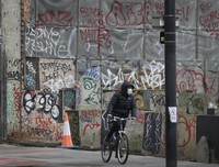 A cyclist wears a mask as he passes graffitti in London, Saturday, Jan. 23, 2021 during England's third national lockdown since the coronavirus outbreak began. (AP Photo/Kirsty Wigglesworth)