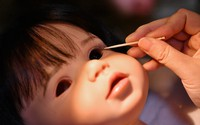 "Using a toothpick, an eyelash is attached to the glass pupil of a ""reborn doll,"" in Sakai, Osaka Prefecture, on Oct. 22, 2020. (Mainichi/Naohiro Yamada)"