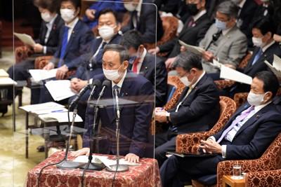 衆院予算委員会で答弁する菅義偉首相(手前)。新型コロナウイルス対策で演台の前には飛沫防止のアクリル板が置かれた=国会内で2021年1月25日午前9時4分、竹内幹撮影
