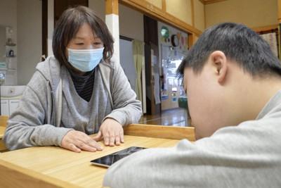 タブレット端末で遊ぶ子どもを優しく見守る菅野友美子さん。震災1カ月後から始めた活動は、間もなく丸10年を迎える=福島県相馬市岩子で、渡部直樹撮影