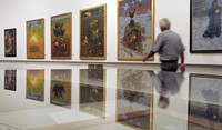"""In this June 22, 2010 file photo, a man walks in front of Arik Brauer's paintings at the exhibition """"Fantastic Art from Vienna"""" in the Panorama museum in Bad Frankenhausen, central Germany. (AP Photo/Jens Meyer)"""
