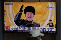 A man wearing a face mask sits in front of a TV screen showing North Korean leader Kim Jong Un, at the Seoul Railway Station in Seoul, South Korea, on Jan. 15, 2021. (AP Photo/Lee Jin-man)