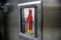In this March 19, 2020 file photo, a biosafety protective suit for handling viral diseases is hung up in a biosafety level 4 training facility at U.S. Army Medical Research and Development Command at Fort Detrick in Frederick, Maryland, where scientists are working to help develop solutions to prevent, detect and treat the coronavirus. (AP Photo/Andrew Harnik)
