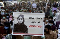 In this Dec. 24, 2020 file photo, supporters of Baloch political activist Karima Baloch hold her portrait during a demonstration to condemn her killing, in Karachi, Pakistan. (AP Photo/Fareed Khan)