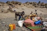 In this Nov. 21, 2020 file photo, refugees who fled the conflict in Ethiopia's Tigray region arrive with their furniture and donkey on the banks of the Tekeze River on the Sudan-Ethiopia border, in Hamdayet, eastern Sudan. (AP Photo/Nariman El-Mofty)