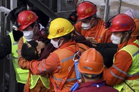 In this photo released by Xinhua News Agency, rescuers carry a miner who was trapped in a mine to an ambulance in Qixia City in east China's Shandong Province, on Jan. 24, 2021. (Chen Hao/Xinhua via AP)