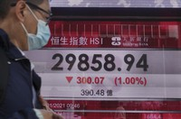 A man walks past a bank's electronic board showing the Hong Kong share index at Hong Kong Stock Exchange on Jan. 26, 2021. (AP Photo/Vincent Yu)