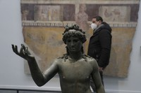 A man walks past the statue of Ephebos inside the museum Antiquarium in Pompeii, southern Italy, on Jan. 25, 2021. (AP Photo/Gregorio Borgia)