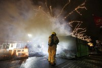 A firefighter extinguishes a a container that was set alight during protests against a nation-wide curfew in Rotterdam, Netherlands, on Jan. 25, 2021. (AP Photo/Peter Dejong)