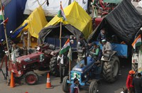 Indian farmers sit on their tractor after arriving at the Delhi-Uttar Pradesh border for Tuesday's tractor rally in New Delhi, India, on Jan. 25, 2021. (AP Photo/Manish Swarup)