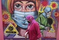 A woman walks past a coronavirus-themed mural honoring health workers in Tangerang, Indonesia, on Jan. 26, 2021. (AP Photo/Tatan Syuflana)