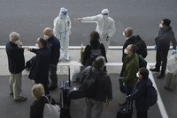 In this Jan. 14, 2021 photo, a worker in protective coverings directs members of the World Health Organization (WHO) team on their arrival at the airport in Wuhan in central China's Hubei province. (AP Photo/Ng Han Guan)