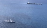 In this undated photo released by Indonesian Maritime Security Agency (BAKAMLA), a BAKAMLA ship escorts Iranian-flagged tanker MT Horse, top right, as they sail towards Batam Island, Indonesia. (Indonesian Maritime Security Agency via AP)