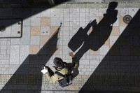 A man wearing a protective mask to help curb the spread of the coronavirus walks along a street in Tokyo on Jan. 19, 2021.  (AP Photo/Eugene Hoshiko)