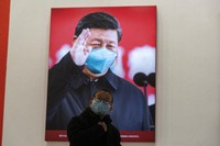 A child wearing a mask reacts near a photo showing Chinese President Xi Jinping at an exhibition on the city's fight against the coronavirus in Wuhan in central China's Hubei province, on Jan. 23, 2021. (AP Photo/Ng Han Guan)