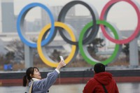 A woman poses for a selfie in front of Olympic rings at Odaiba waterfront in Tokyo, on Jan. 26, 2021. (AP Photo/Koji Sasahara)