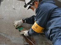 A preservation worker checks brick colors as part of wall repairs at the Atomic Bomb Dome in Hiroshima's Naka Ward on Jan. 27, 2021. (Mainichi/Naohiro Yamada)