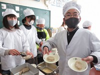 A student shows crocodile meat patties at Kokumei Elementary School in Toyonaka, Osaka Prefecture, on Jan. 26, 2021. (Mainichi/Mari Misumi)