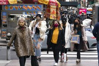 Women carry shopping bags on Dec. 10, 2020, in New York. The spread of COVID-19 vaccines will power a stronger global economic recovery in 2021, the International Monetary Fund forecast on Jan. 26, 2021. (AP Photo/Mark Lennihan)