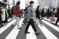 People wearing protective masks to help curb the spread of the coronavirus walk along a pedestrian crossing on Jan. 26, 2021, in Tokyo. (AP Photo/Eugene Hoshiko)