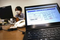 A computer screen shows a data image for a vaccination coupon at the local office for COVID-19 vaccination preparation at Tokyo's Sumida Ward office on Jan. 22, 2021. (AP Photo/Eugene Hoshiko)