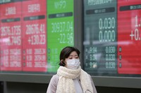 A woman walks by an electronic stock board of a securities firm in Tokyo on Jan. 27, 2021. (AP Photo/Koji Sasahara)