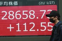 A man walks by an electronic stock board of a securities firm in Tokyo on Jan. 27, 2021. (AP Photo/Koji Sasahara)
