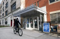 In this Jan. 21, 2021, file photo, a cyclist passes a closed vaccination center at the George Westinghouse High School in New York. (AP Photo/Mark Lennihan)
