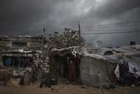 A Palestinian woman checks the nylon cover on the roof of her house on a rainy day in a poor neighborhood of Khan Younis, in the southern Gaza Strip, on Jan. 20, 2021. (AP Photo/Khalil Hamra)