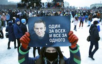 This file photo, Jan. 23, 2021, a man holds a poster with a portrait of Alexei Navalny that reads: 'One for all and all for one', during a protest rally against the jailing of opposition leader Alexei Navalny in St. Petersburg, Russia. (AP Photo/Dmitri Lovetsky)
