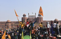 Sikhs wave the Nishan Sahib, a Sikh religious flag, as they arrive at the historic Red Fort monument in New Delhi, India, on Jan. 26, 2021. (AP Photo/Dinesh Joshi)