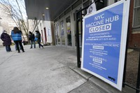In this Jan. 21, 2021 photo, people who had appointments to get COVID-19 vaccinations talk to New York City health care workers outside a closed vaccine hub in the Brooklyn borough of New York after they were told to come back in a week due to a shortage of vaccines. (AP Photo/Kathy Willens)