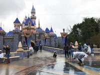 In this March 13, 2020 file photo, visitors take photos at Disneyland in Anaheim, Calif. (AP Photo/Amy Taxin)