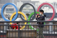 People wearing face masks to protect against the spread of the coronavirus stand at the Odaiba waterfront as Olympic rings is seen in the background in Tokyo, on Jan. 26, 2021. (AP Photo/Koji Sasahara)