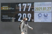 A woman walks past a countdown clock for Tokyo Olympic and Paralympic Games in Tokyo on Jan. 27, 2021. (AP Photo/Koji Sasahara)