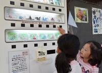 Children gather in front of an origami vending machine placed before Okano Shoten in Uchiko, Ehime Prefecture, on Oct. 21, 2020. (Mainichi/Tomoe Saito)
