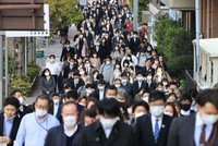 Crowds of people are seen wearing masks on their way to work in Tokyo's Chuo Ward on April 8, 2020. (Mainichi/Naotsune Umemura)