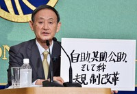 Yoshihide Suga, then a candidate for prime minister, is seen at a candidates' debate for the Liberal Democratic Party Presidential Election at the Japan National Press Club in Tokyo's Chiyoda Ward on Sept. 12, 2020. The board in his hand roughly translates to