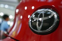 In this Aug. 2, 2019, file, photo, people walk by the logo of Toyota at a show room in Tokyo. (AP Photo/Eugene Hoshiko)