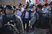 Ultra-Orthodox Jews argue with Israeli border police officers during a protest over the coronavirus lockdown restrictions, in Ashdod, Israel, on Jan. 24, 2021. (AP Photo/Oded Balilty)