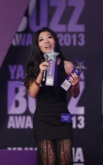 In this Dec. 1, 2013 file photo, Chinese singer-songwriter Wanting Qu holds two trophies after winning Hong Kong Most Popular Singer-Songwriter and the Best Mandarin Song at the Yahoo Buzz Awards in Hong Kong. (AP Photo/Kin Cheung)