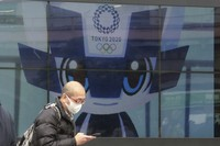A man walks by an electric monitor promoting the Tokyo 2020 Olympics planned to start in the summer of 2021, in Tokyo, on Jan. 27, 2021. (AP Photo/Koji Sasahara)