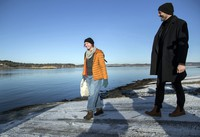 Lisa Enroth, left, prepares to depart for the island of Hamneskar, western Sweden as she speaks with Jonas Holmberg, creative director of the Goteborg Film Festival, on Jan. 30, 2021. (AP Photo/Thomas Johansson)