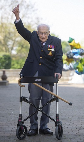 In this April 16, 2020 file photo, Captain Tom Moore gestures after achieving his goal of 100 laps of his garden, at his home in Marston Moretaine, England. Tom Moore, the 100-year-old World War II veteran who captivated the British public in the early days of the coronavirus pandemic with his fundraising efforts, has died, Tuesday Feb. 2, 2021. (Joe Giddens/PA via AP)