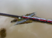 A train passes a rail road crossing that is surrounded by flooding caused by rain and melting snow in Nidderau near Frankfurt, Germany, on Feb. 3, 2021. (AP Photo/Michael Probst)