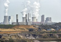 In this April 3, 2014 file photo giant machines dig for brown coal at the open-cast Garzweiler mine in front of a smoking power plant near the city of Grevenbroich in western Germany. (AP Photo/Martin Meissner)