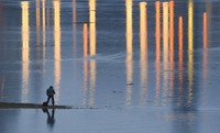 A man takes pictures of the flooded meadows near the river Elbe in Dresden, Germany, on Feb. 5, 2021. (Robert Michael/dpa via AP)