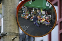 A man wearing a protective mask is reflected on a traffic mirror as he walks on a street on Feb. 5, 2021, in Tokyo. (AP Photo/Eugene Hoshiko)